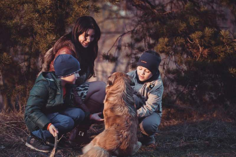 Woman helps her children with dog training and care